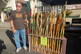 DOUG WHITE from Natomas brought his hand-painted walking sticks to sell at the Craft Fair in downtown Placerville Sunday. The sticks are made from willow branches. Democrat photo by Krysten Kellum